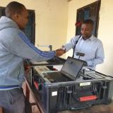 BVR Kit Operator katika kituo cha kuandikisha Wapiga Kura cha Ofisi ya KNCU Kyala Wilaya ya Moshi Vijijini Bw. Willy Nzenga akimkabidhi Kadi ya Mpiga Kura mmoja wa Wapiga Kura aliyerekebisha taarifa zake wakati wa Uboreshaji wa Daftari la Kudumu la Wapiga Kura kwa mikoa ya Kilimanjaro na Arusha.